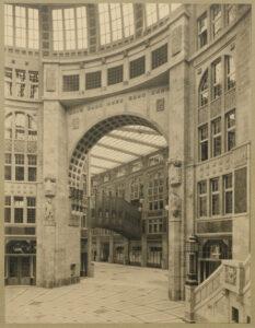 """Architektonische Spielerei im Passage-Kaufhaus, 1908. Blick aus dem Kuppelraum in den Passage-Arm Richtung Oranienburger Straße auf die zweistöckige """"Rialto""""-Brücke."""
